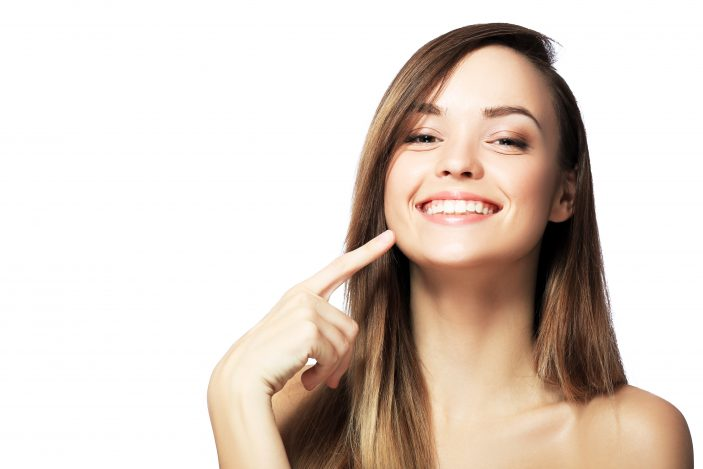 woman in front of white background smiling and pointing at her teeth