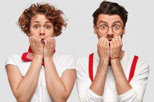 A surprised man and woman with their hands over their mouths