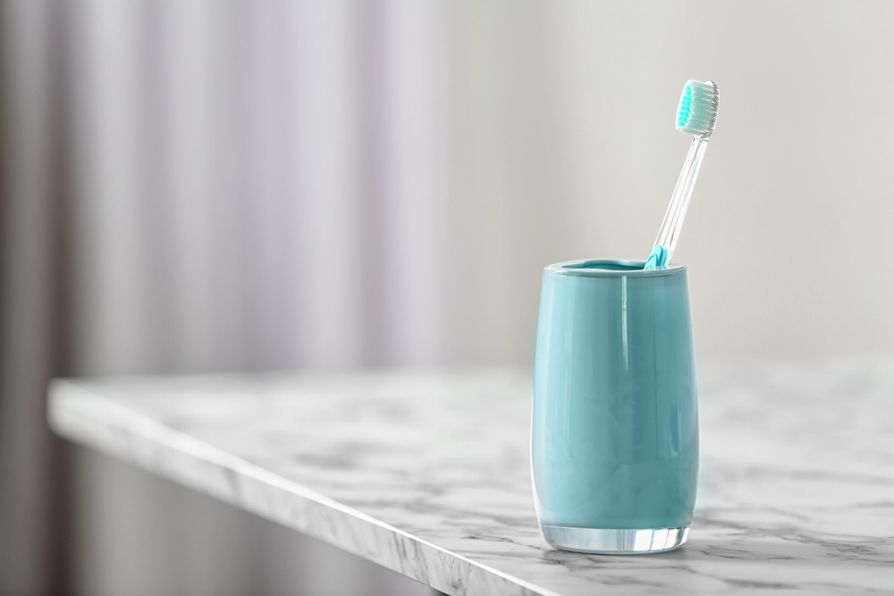 toothbrush in a toothbrush cup on a marble counter