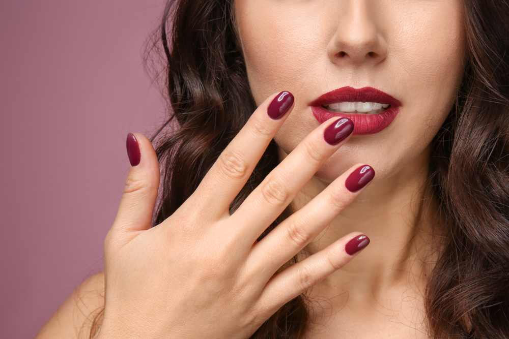 A woman holding up her painted fingernails by her mouth