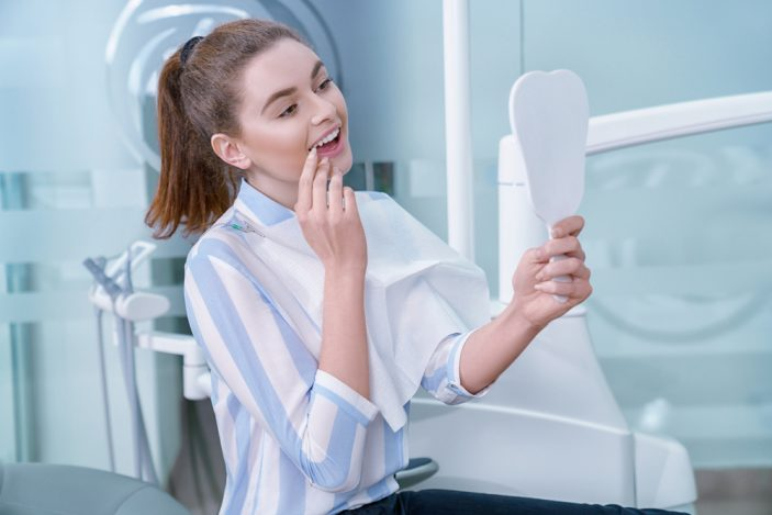 A woman looking at her teeth in a mirror and touching one of her teeth