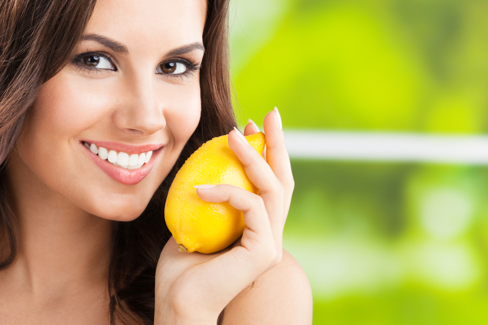 A woman holding a lemon by her face and smiling