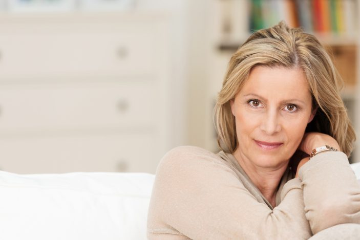 A middle aged woman sitting on a couch resting her head on her arms