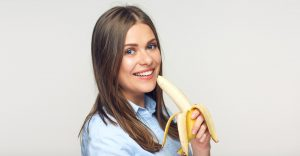A woman holding a banana and smiling
