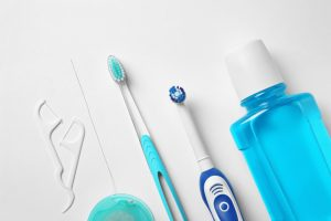 floss, a manual toothbrush, an electric toothbrush, and mouthwash laying on a white surface