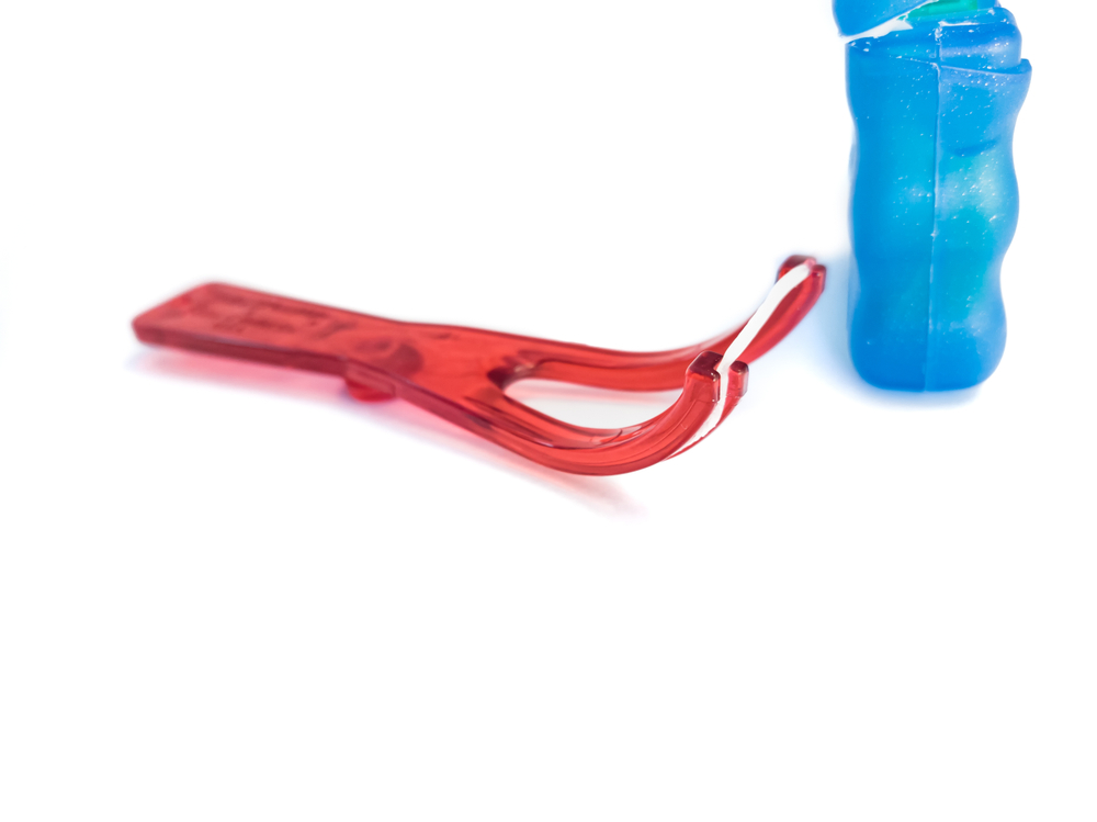 a red floss holder laying on a white surface next to a blue container of floss
