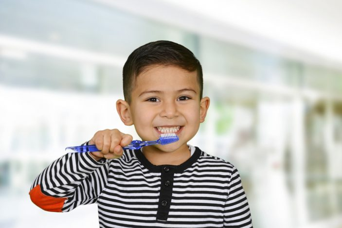 A young boy brushing his teeth and smiling