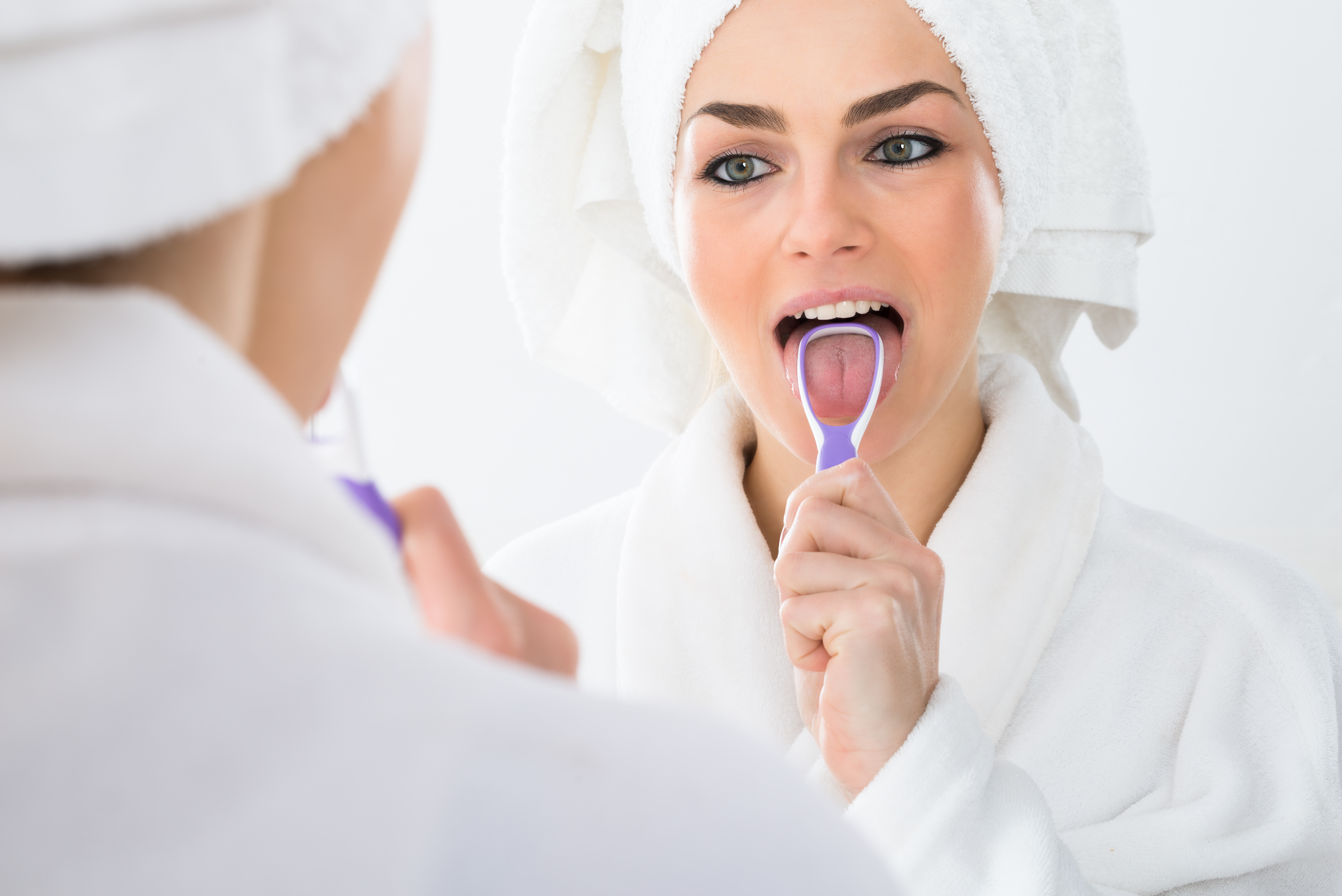 woman wearing a white bathrobe and a white towel on her head using a tongue scraper