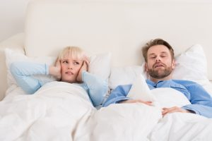 blonde woman laying in bed covering her ears as her male partner lays in bed beside her sleeping