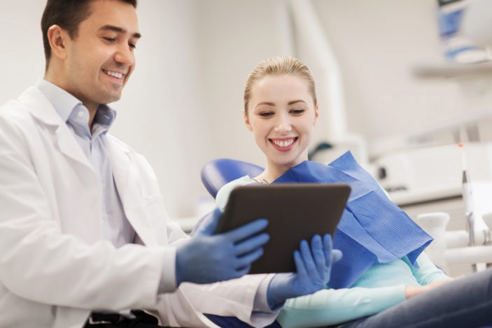 woman with blonde hair sitting in a dental chair smiling at a screen a dentist is showing her as he smiles too
