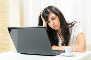 woman with dark hair sitting at a desk and looking at a laptop while bored