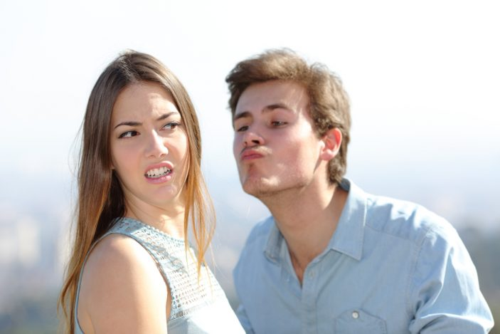woman rejecting a kiss from a man