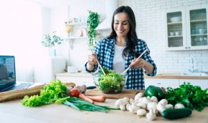 A woman preparing a salad and smiling