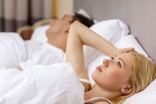 A woman laying in bed awake next to her husband