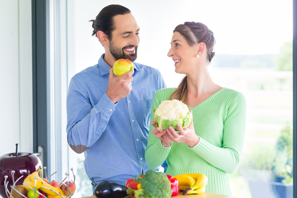 A man and woman smiling at eachother and holding fruits and veggies