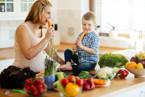 A mother and her son in the kitchen eating vegetables