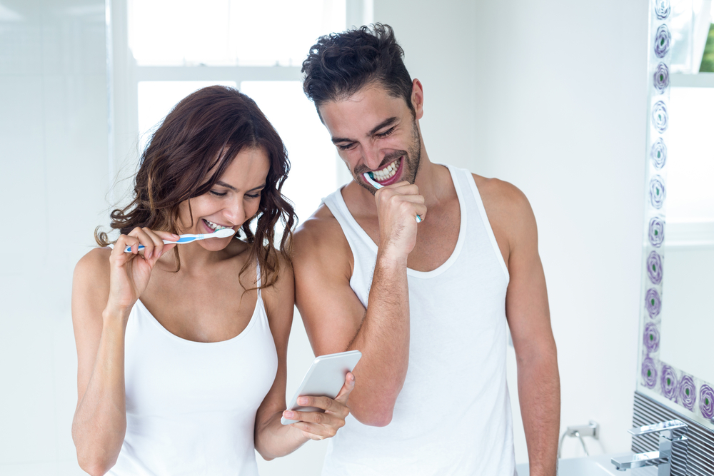 A man and woman looking at a phone and brushing their teeth