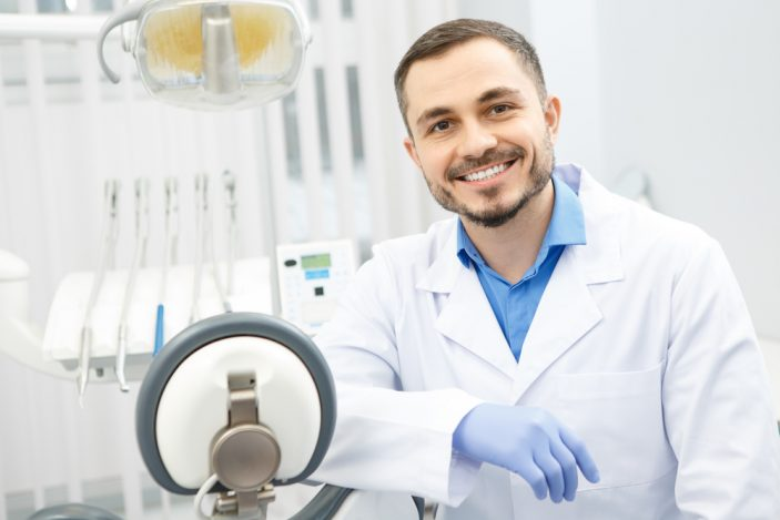 male dentist sitting in an exam room and smiling