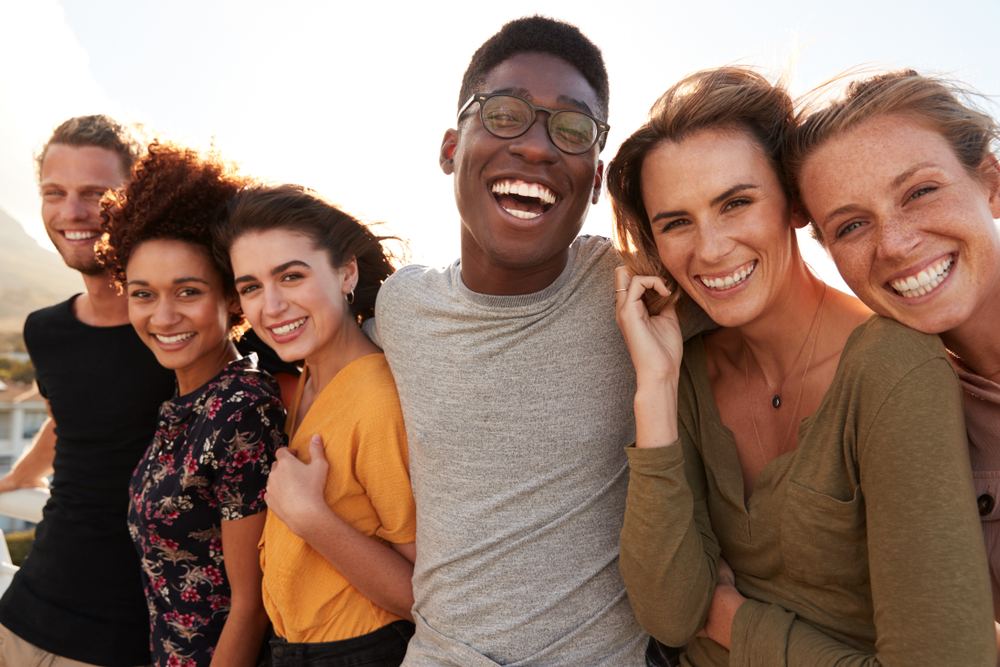 diverse group of friends all hugging and smiling outside